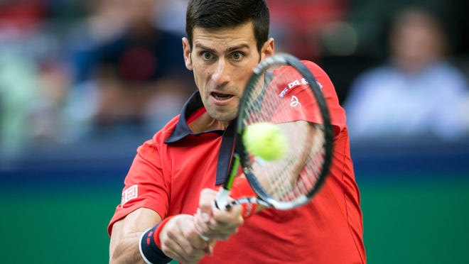 Novak Djokovic of Serbia hits a return shot against Feliciano Lopez of Spain during their Shanghai Masters match.