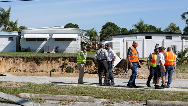Emergency workers assess an area where a 60-foot-wide sinkhole opened on Wednesday in a Pinellas County utilities easement bordering the south side of the Tarpon Shores Mobile Home Park in Tarpon Springs.