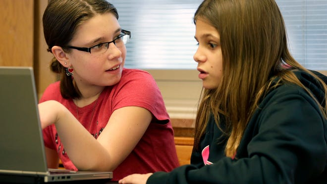 Foster Elementary School students Makaila Steidl (left) and Caitlynn Johnson work on a website they will use to generate awareness of global issues.