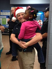 Kim Mixon, a Pineville police officer, holds 3-year-old