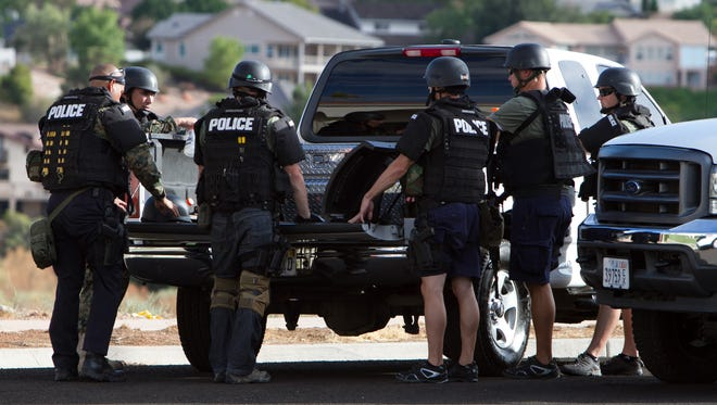 St. George Police Department SWAT team member discuss their strategy during a standoff between police and a man inside a car with a gun near the St. James Place trailhead Saturday, August 2, 2014.
