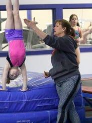 Elmira Gymnastics Club coach Brenna Woolhiser works