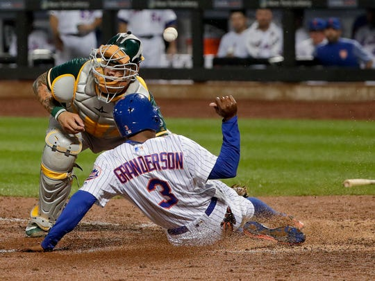 New York Mets' Curtis Granderson (3) slides safely into home plate as the ball skips away from Oakland Athletics catcher Bruce Maxwell during the sixth inning of a baseball game, Saturday, July 22, 2017, in New York. Grandson scored on a double by Michael Conforto.