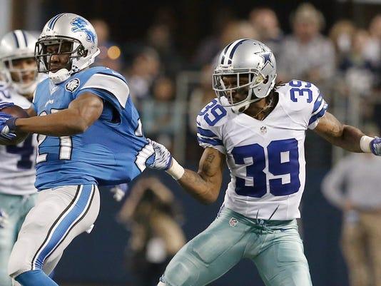 Dallas Cowboys cornerback Brandon Carr (39) tries to stop Detroit Lions running back Reggie Bush (21) during the second half of an NFL wildcard playoff football game, Sunday, Jan. 4, 2015, in Arlington, Texas. (AP Photo/Brandon Wade)