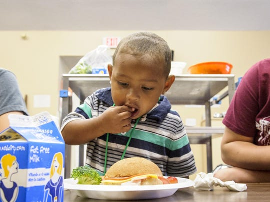 Damontay Evans gets his tummy full at lunch eating grapes and other fresh foods under the watchful eyes of volunteers Camden Christensen and Tricia Sills. Kids Cafe is the only USDA Summer Food Service Program that serves children within the Southeast Polk Community.