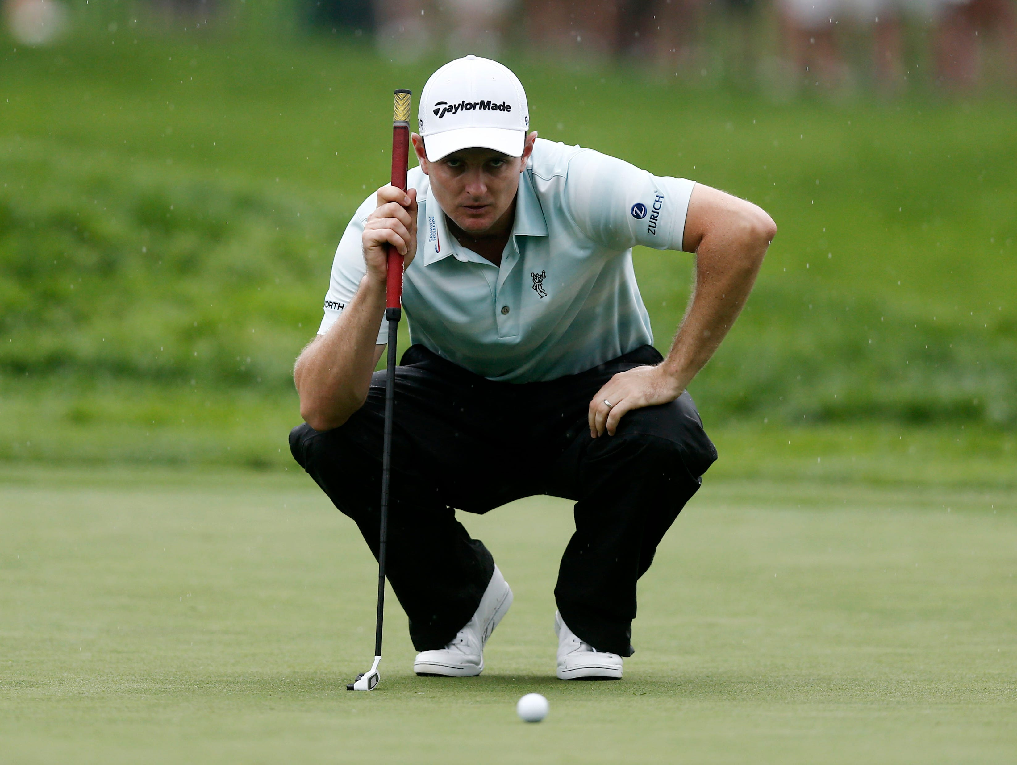 Justin Rose lines up his putt on the 11th green.