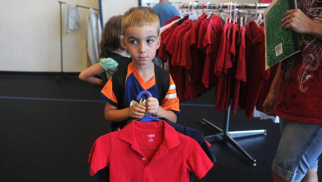 Connor Moore, 5, holds polo shirts his parents bought for his school uniform in Evansville, Ind., on Aug. 5.