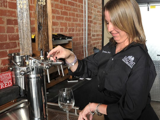 Half Pint Taproom & Restoration Hall co-owner Cynthia Doten tests the wine taps the location will feature after their Monday evening grand opening.