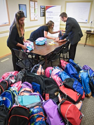 Nakina Gross, left, Carrie Seanger and Spencer Linn show items that they purchased and placed into backpacks for area children in need Wednesday, Aug. 10, at Primerica Financial Services in Sauk Rapids.