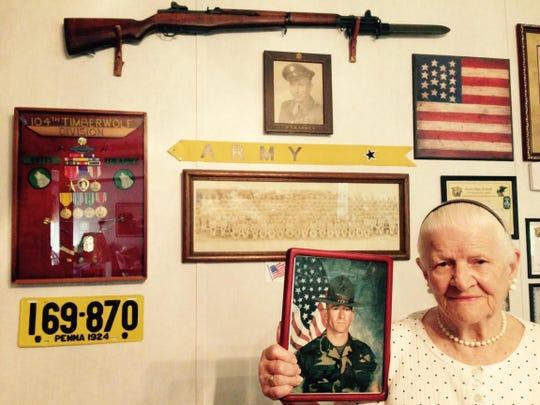 Martha Butts of Colfax holds a photo of her son, Carlos, from when he was in the Marines as she stands in front of a wall in her home that has memorabilia from her family's military service, including that of her husband, Gilburn (shown in framed photo on the wall). She has written patriotic poetry, including poems about how Carlos carried a small American flag that she and Gilburn gave him around the world during his 23-year career in the Marines.