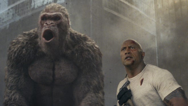 "George the gorilla (Jason Liles is in the motion-capture suit) and Dwayne Johnson hit the town in ""Rampage."""