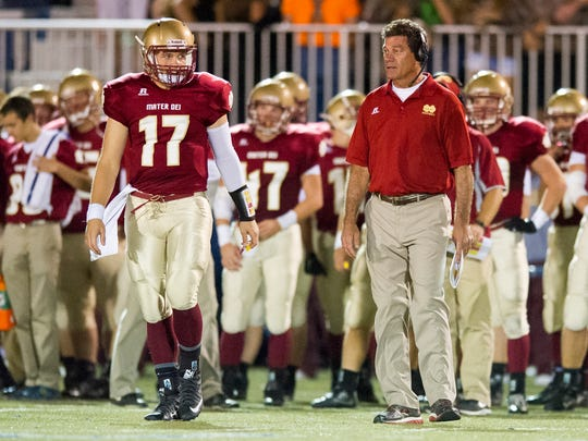 Mater Dei's Kurtis Wilderman (17) speaks with head coach Mike Goebel during their game against Central at the Reitz Bowl in Evansville, Friday, Oct. 7, 2016. Central beat Mater Dei 56-17.