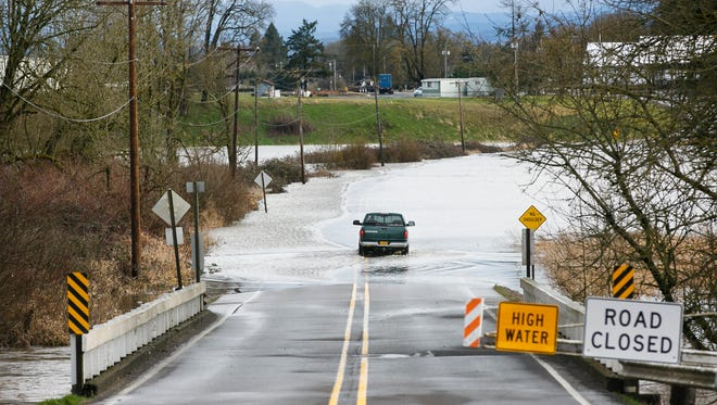 A truck drives through water flooding over Hazelgreen Road NE near Torvend Road, just west of Silverton, on Thursday, Feb. 9, 2017. The driver was stopped by police after passing through the water.