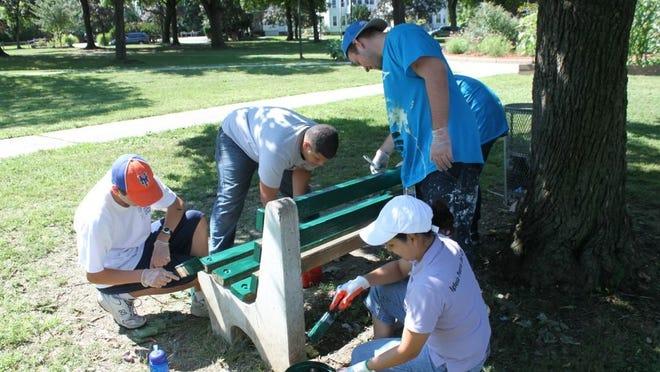 Bridge Builders volunteers paint a bench in Waryas Park in 2012.