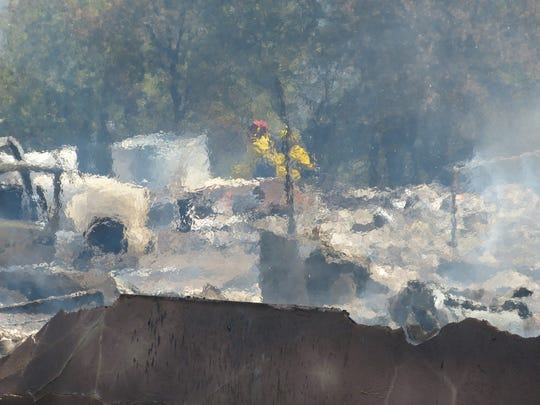 Heat radiates off the scorched rubble of a home and adjacent structures destroyed in a Friday fire in Oak Run.