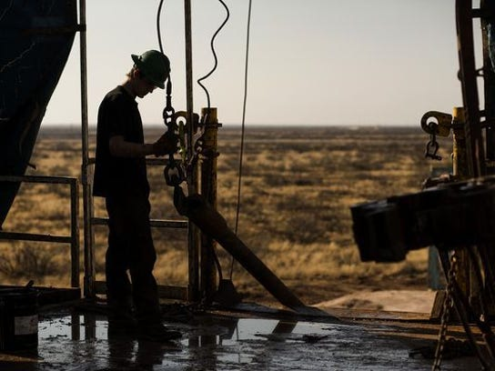 A worker prepares to hoist a joint of drill-stem pipe