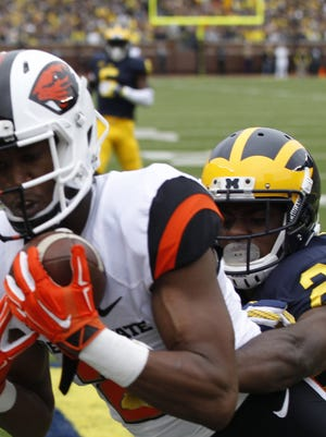 Oregon State's Hunter Jarmon catches a 21-yard touchdown pass in front of Michigan's Jourdan Lewis in the first quarter Saturday at Michigan Stadium.