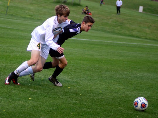 Gallatin High sophomore Will Stevens and Hendersonville senior Owen Kalada battle for a 50-50 ball during first-half action. Kalada scored on a penalty kick in the Commandos' 2-0 victory.