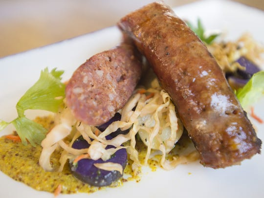The house-made Kielbasa sausage is served on a bed of sauerkraut and potato salad at The Emporium on Tuesday, December 12, 2017.