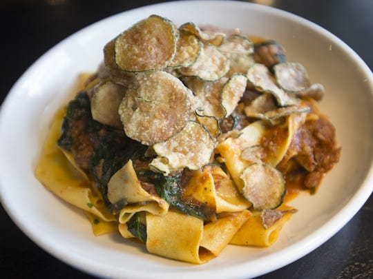 A plate of braised lamb is served with pappardelle