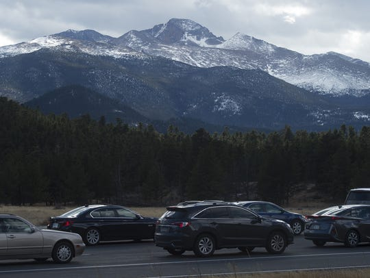 Longs Peak rises above a line of cars waiting at the