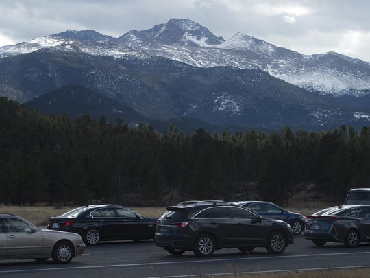 Longs Peak rises above a line of cars waiting at the Beaver Meadows entrance station to enter Rocky Mountain National Park on Friday, November 24, 2017.