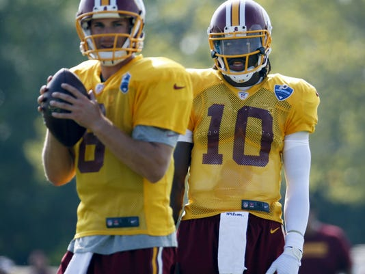 Kirk Cousins, seen here preparing to pass during practice, has supplanted Robert Griffin III, right, as the Washington Redskins' starting quarterback.