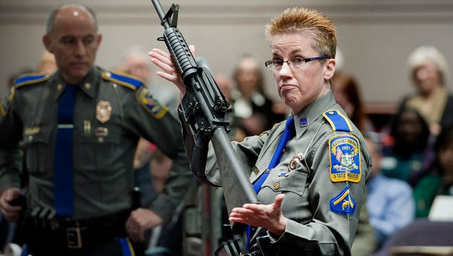Firearms training unit Detective Barbara J. Mattson, of the Connecticut State Police, holds up a Bushmaster AR-15 rifle, the same make and model of gun used by Adam Lanza in the Sandy Hook School shooting, during a hearing of a legislative subcommittee in Hartford, Conn., Jan. 28, 2013.