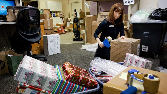 Owner Judy Redmond boxes up Christmas gifts to be shipped Friday at the UPS Store in the Pine Grove Plaza Shopping Center.