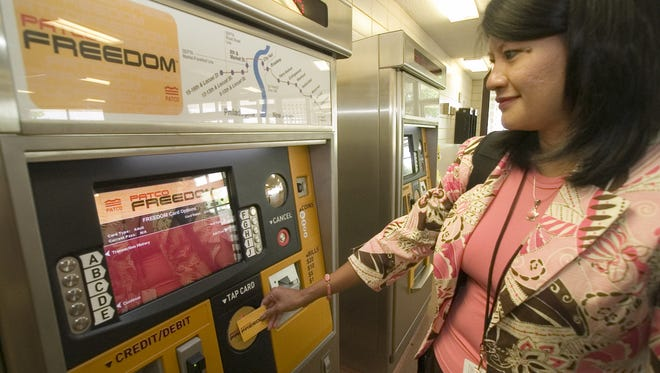 A PATCO employee demonstrates the fare collection system in this 2006 file photo.