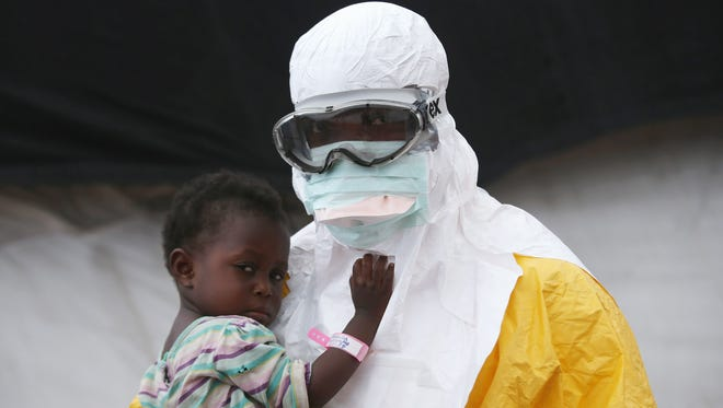 A Doctors Without Borders health worker in protective clothing holds a child suspected of having Ebola in a Liberia treatment center on October 5, 2014.