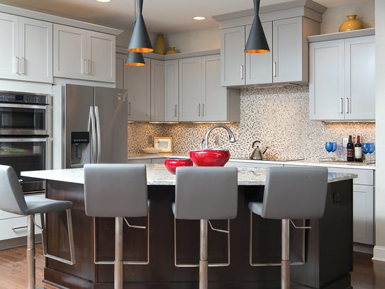 Outer kitchen cabinets are dove gray, topped by a white-and-gray