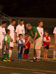 George Herrick, third from right, shakes hands with youth soccer players at the Sept. 25 Vestal varsity boys soccer game. Herrick coached in Vestal for 29 years and also helped start the Vestal Youth Soccer program.
