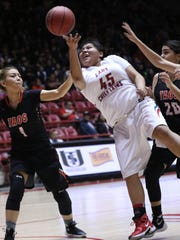 Shiprock's Keishonna Begay is fouled by Taos' Elicia Sanchez (20) and Lillian Cordova (1) during their 4A state quarterfinal game on Tuesday at The Pit in Albuquerque.