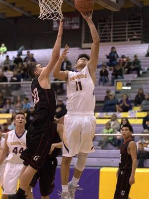 Kirtland Central's Terrin Willie drives past Grants' Kevin Siera for a layup on Saturday at Bronco Arena in Kirtland.