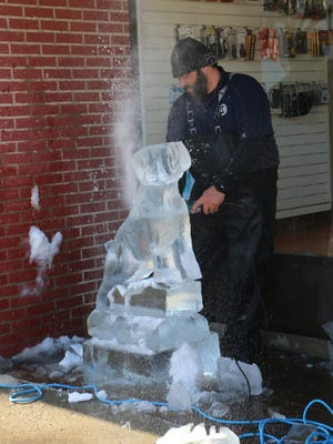 Two ice carvers will be in Wellsboro on Saturday to create six different sculptures from six 450-pound blocks of ice. Shown in this photo is one of them at work on carving a dog from ice during last year's celebration.