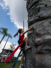 Kenna Gallo, 6, works her way up a rock climbing wall