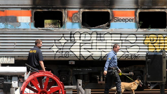 Morris County Sheriff's Detective Cpl. Michael McMahon and K9 Cinders investigate for accelerants on a Parlor and a Sleeper train at the Whippany Railway Museum in Whippany. The two historic railroad cars were taken to the museum yard after they were destroyed overnight in a fire in East Hanover. August 4, 2017. Whippany, NJ