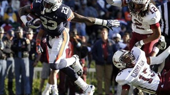 Auburn running back Onterio McCalebb (23) breaks free from Alabama A&M defensive backs Julius Williams (15) and defensive back Jeremy Isabelle (12) for a touchdown during the second half of an NCAA college football game on Saturday, Nov. 17, 2012 in Auburn, Ala.