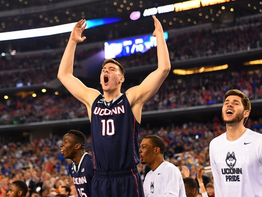 Tyler Olander (10) celebrates his team about to win from the bench in the second half as the Connecticut Huskies beat the Florida Gators 63-53 in the first semifinal game of the Final Four at AT&T Stadium Saturday, April 5, 2014 in Arlington, Texas.