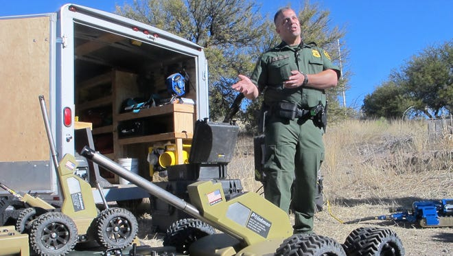 U.S. Border Patrol Agent Kevin Hecht, a tunnel expert, discusses the force's latest technology in the drug war _ a wireless, camera-equipped robot, during a briefing in Nogales, Ariz., Tuesday, Jan. 14, 2014.  With more than 75 underground drug smuggling tunnels found along the border since 2008, mostly in California and Arizona, the Border Patrol is utilizing the robots to search deep underground while keeping agents safer. (AP Photo/Brian Skoloff)