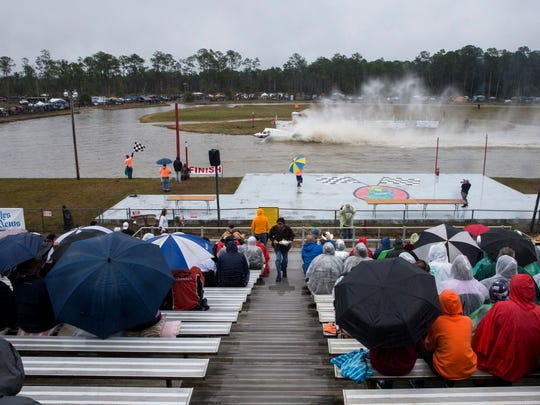 Fans watch as Backdraft crosses the finish line during the Budweiser Winter Classic swamp buggy races at Florida Sports Park in Naples, Florida on Sunday, Jan. 29, 2017.