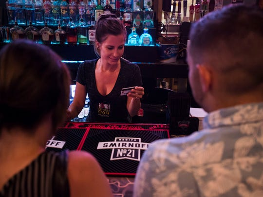 Bondi Beach Bar and Grill bartender Alisha Pecchenino checks the IDs of Emma Cook and Garrett Wahlen at the bar on Friday, June 15, 2018, in Old Town Fort Collins, Colo.