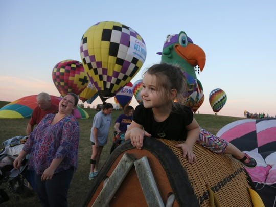 Elin Reinert, 3, of Ankeny climbs on a basket at the