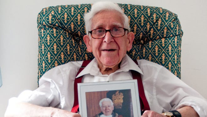 Bernard Jordan, an 89-year-old British navy veteran, at the nursing home in Hove holding a picture of himself when he was the town's mayor from 1995 to 1996.