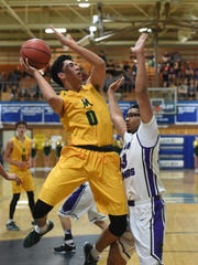 Bishop Manogue's Brevon Bansuelo goes up to shoot with Spanish Spring's Marcus Loadholt covering him in Thursday's at Carson.