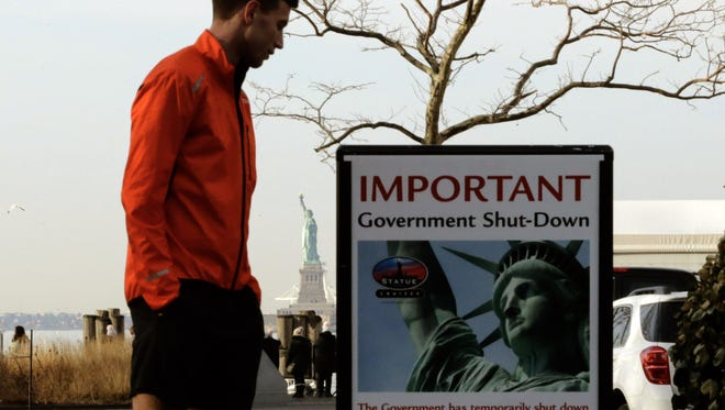 A man reads the shutdown alert at the Liberty State ferry terminal in Battery Park on Sunday in New York City. The iconic landmark remains closed as part of the U.S. government shutdown.