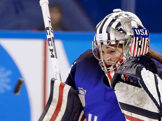In this Feb. 13, 2018 photo, goalie Nicole Hensley, of the United States, deflects the puck during the preliminary round of the women's hockey game against the team from Russia at the 2018 Winter Olympics in Gangneung, South Korea. Goaltenders are the only players in Olympic hockey allowed to get creative with decorating their helmets. Their teammates are stuck with helmets featuring basic colors, uniform numbers and a small flag decal representing their country. (AP Photo/Matt Slocum)