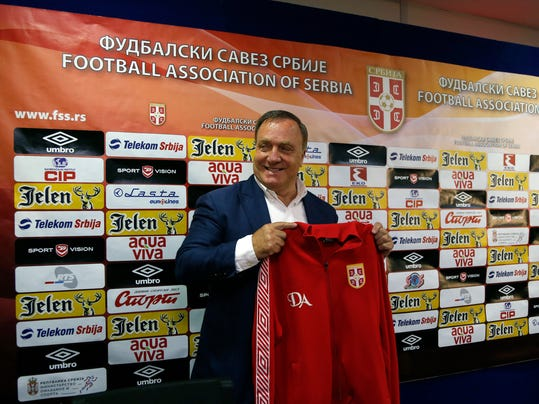 Newly-appointed Serbian national soccer team coach Dick Advocaat poses for photographers with a  Serbian jersey  during a press conference in Stara Pazova, Serbia, Monday, July 28, 2014. Advocaat signed a two-year contract with Serbia and has the mandate to lead them to the 2016 European Championship in France. (AP Photo/Darko Vojinovic)