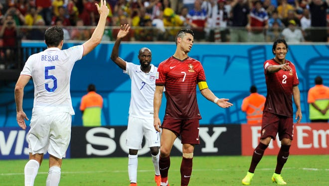 Portugal's Cristiano Ronaldo, center, and Portugal's Bruno Alves, right, react to a play along with United States' Matt Besler, left, and United States' DaMarcus Beasley, second from left, during the group G World Cup soccer match between the USA and Portugal at the Arena da Amazonia in Manaus, Brazil, Sunday, June 22, 2014. (AP Photo/Paulo Duarte)
